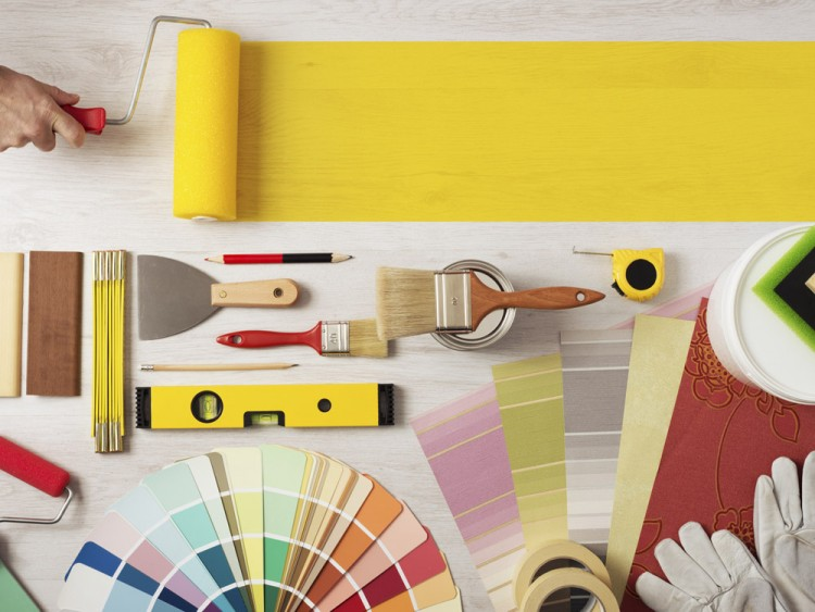 Decorator holding a painting roller and painting a wooden surface, work tools and swatches at bottom.